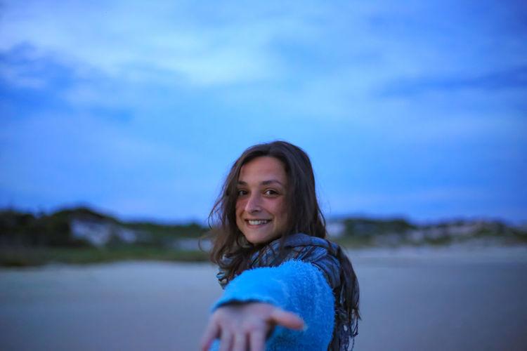 Portrait of smiling woman against blue sky