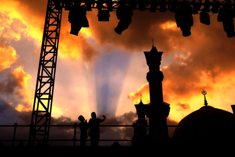 Low angle view of silhouette friends by mosque against orange sky