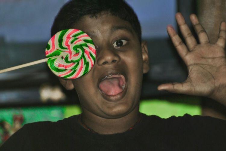 Portrait of shocked boy covering eye with lollipop
