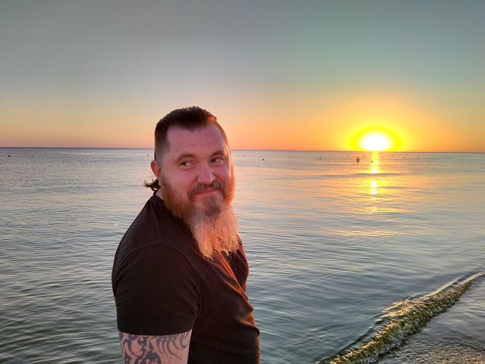 Portrait of man in sea against sky during sunset