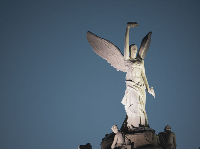 Low angle view of angel statue against clear sky