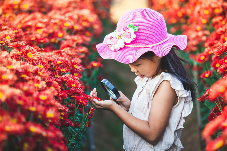 Side view of girl wearing hat looking flower through magnifying glass on field