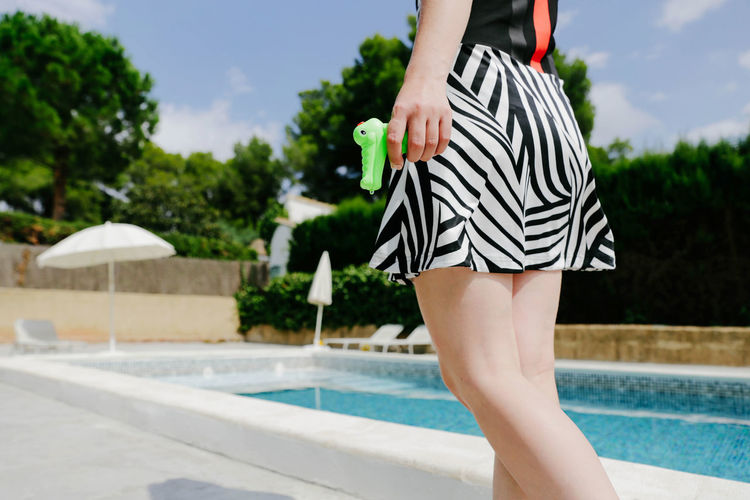 Midsection Of Young Woman Holding Squirt Gun By Swimming Pool