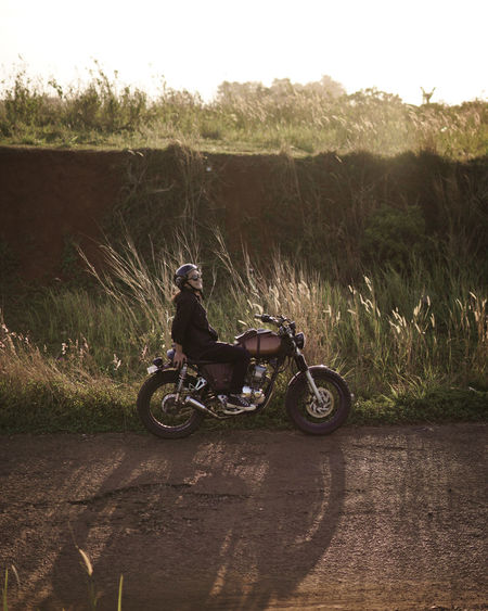 Smiling woman sitting on motorcycle against grass