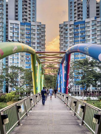 People on footbridge amidst buildings in city