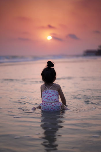 Rear view of girl at beach against sky during sunset