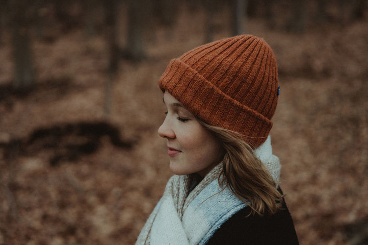 Side view of woman with knit hat and eyes closed at park during autumn