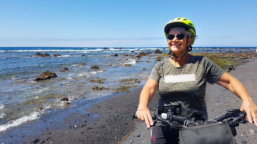 Senior woman riding bicycle on beach