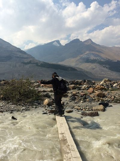 Full Length Rear View Of Person Walking Over River Against Mountains