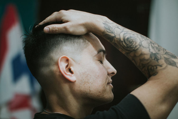 Close-up of young man with hand in hair while siting at barber shop