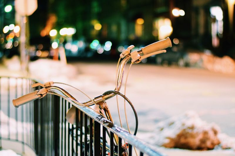 Bicycle parked by railing on street