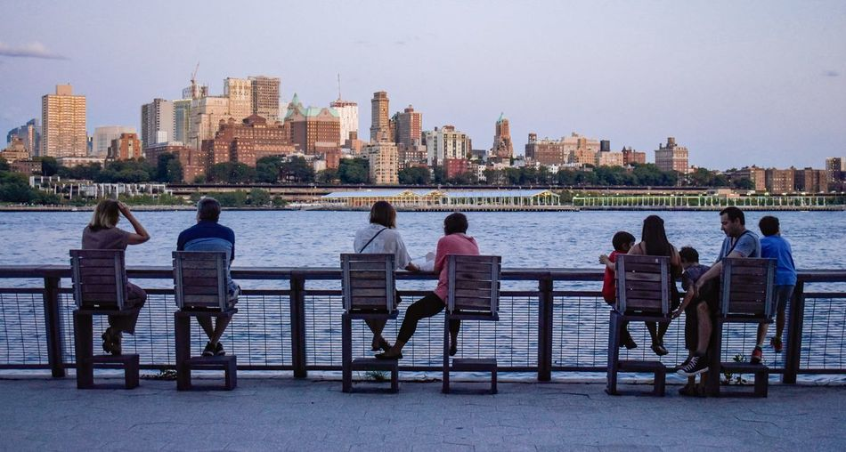 People sitting on bench by river in city
