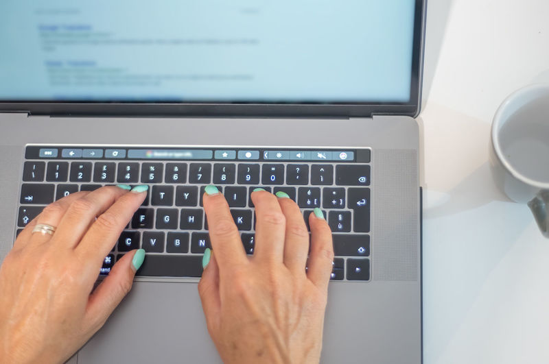 Low section of person using laptop on table