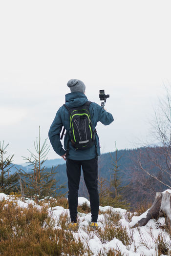 Rear view of man photographing during winter