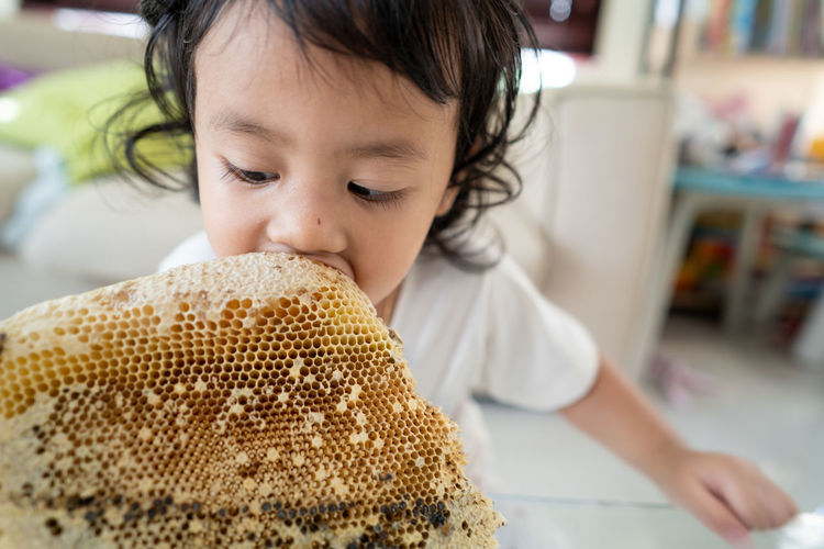 Close-up of girl eating honey from honeycomb