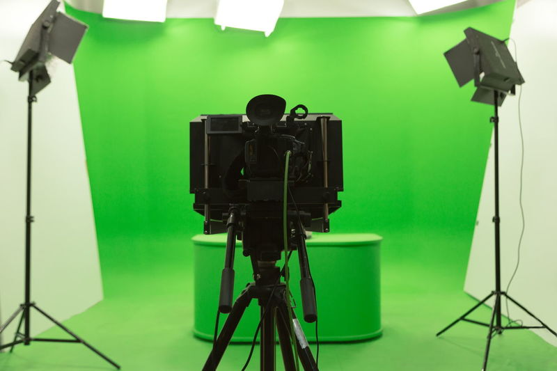 Modern TV Studio Green Screen chroma key background with camera and Light Equipment Arts Culture And Entertainment Behind The Scenes Camera - Photographic Equipment Creativity Digital Camera Electric Lamp Equipment Film Industry Film Studio Filming Indoors  Lighting Equipment No People Photo Shoot Photographic Equipment Photographing Photography Themes Preparation  Studio Studio Shot Technology Television Camera Television Studio The Media Tripod