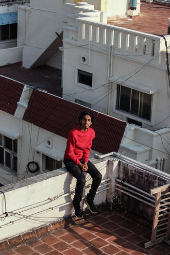Full length portrait of young man standing on staircase of building