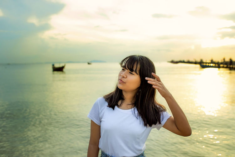 Girl looking away against sea at sunset