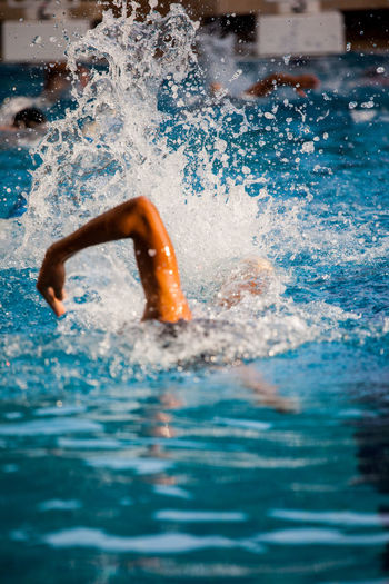 Cropped image of male swimmer swimming in pool during competition