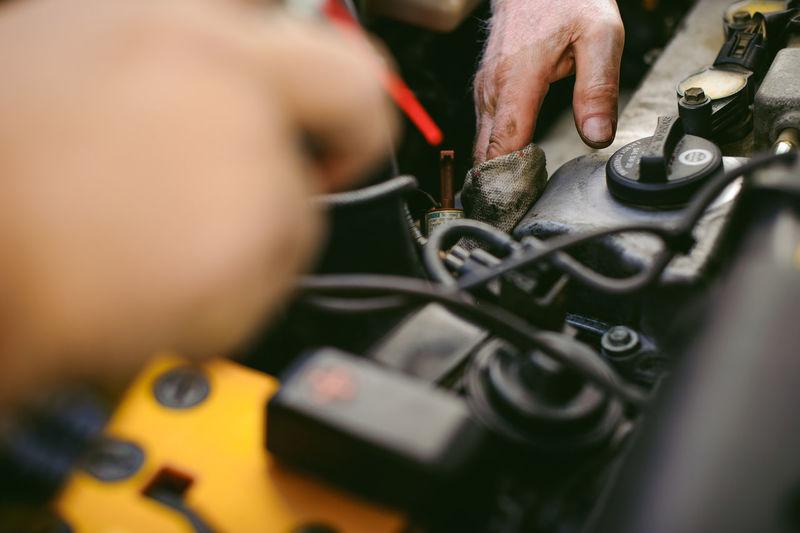 Cropped Hands Of Mechanic Repairing Engine