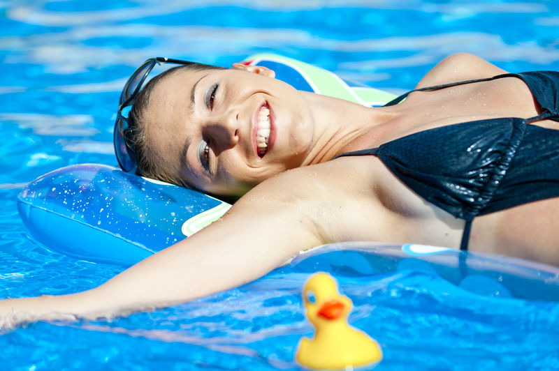 Portrait Of Sensuous Woman Relaxing On Raft In Swimming Pool