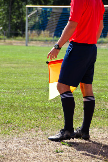 Low Section Of Soccer Player With Flag Standing On Field