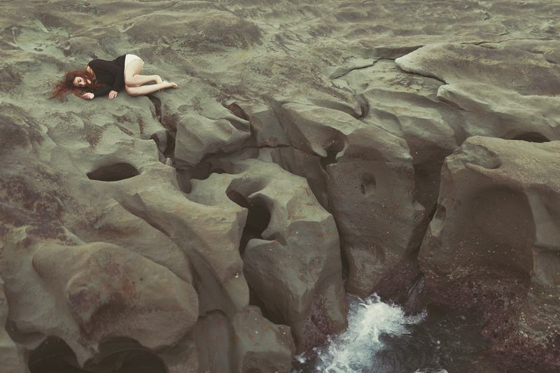Woman lying on rock formation at sea
