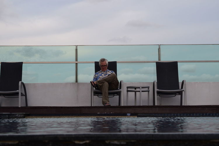 Senior man sitting on chair at poolside against cloudy sky