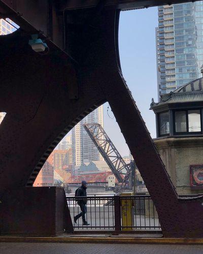 Man on bridge against modern buildings in city