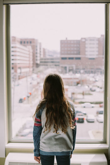Modern Day Girl Indoors  Long Hair Looking Out Window One Person People Reading Book Real People Young Girl Looking Out Window Young Girl Reading