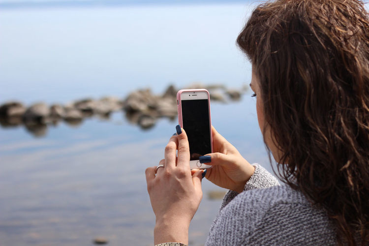 Rear view of woman photographing with mobile phone at beach