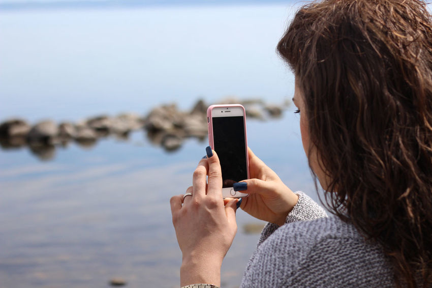 Cellphone Communication Day Focus On Foreground Holding Horizon Over Water Leisure Leisure Activity Mobile Phone Nature One Person Outdoors Photographing Photography Themes Portable Information Device Real People Rear View Sea Smart Phone Technology Touch Screen Using Phone Water Wireless Technology Women
