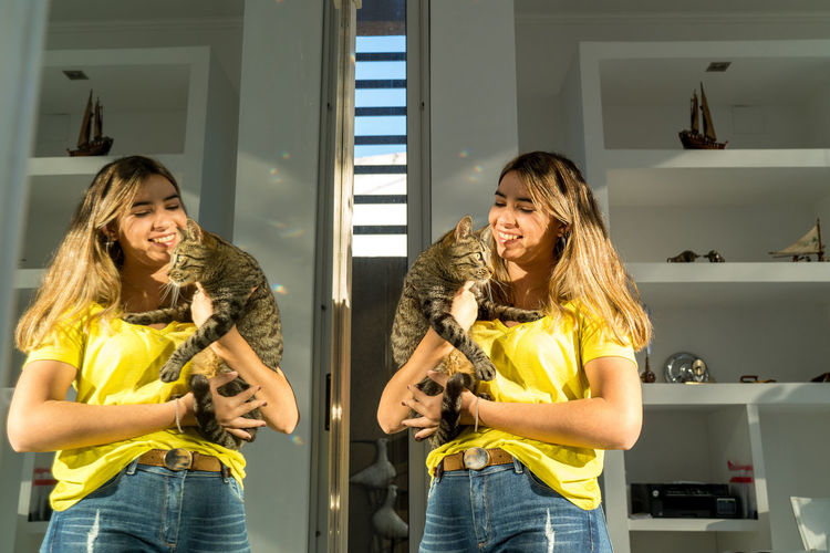 Young woman in front of the mirror with her pet cat