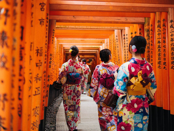 Rear View Of Women In Kimono Walking Under Torii Gate