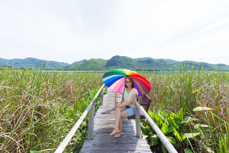 Young woman sitting on bench at boardwalk over grass against sky