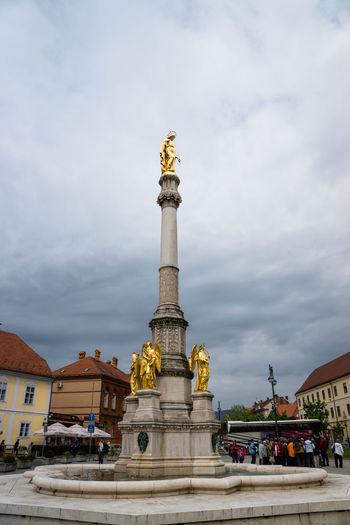 Holy mary column amidst town against cloudy sky in croatia