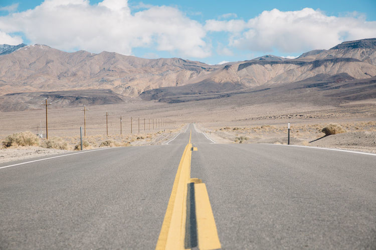 Empty road in desert against sky