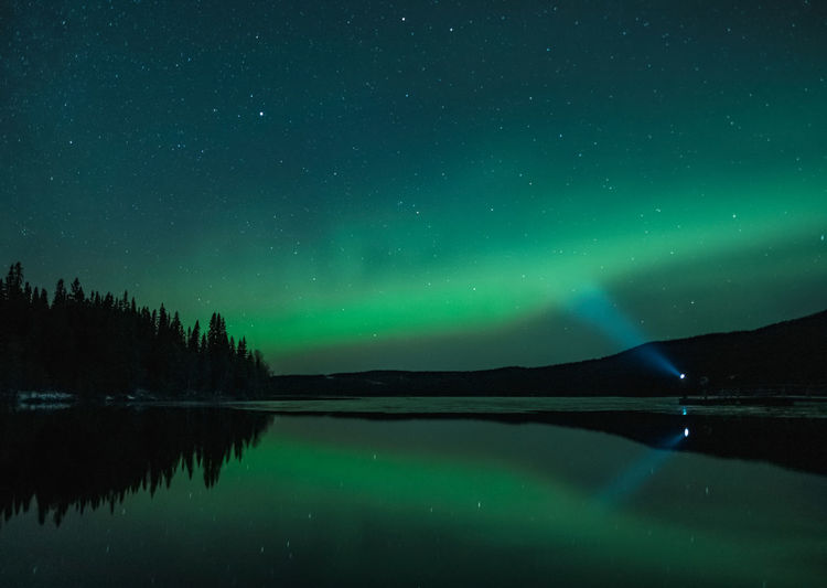 Scenic aurora view of lake against star field at night