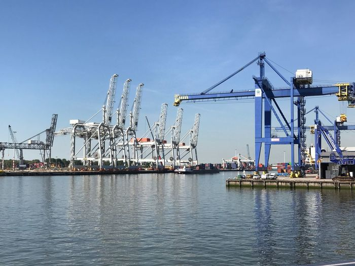 Cranes at harbor against clear blue sky