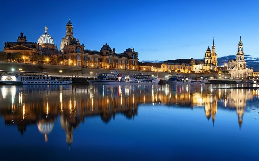 River By Illuminated Buildings And Dresden Cathedral At Dusk
