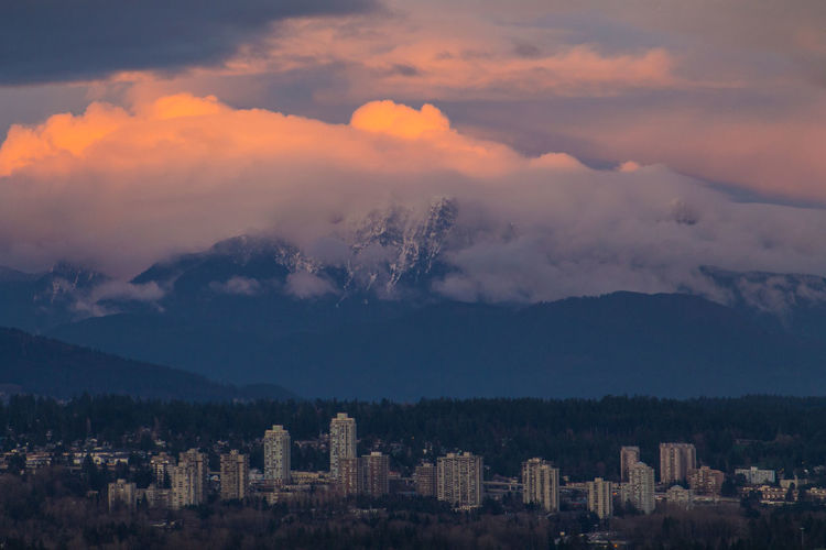 Snowcapped Mountain and the City Atmosphere Atmospheric Mood Cloud Cloud - Sky Cloudscape Cloudy Community Dramatic Sky Human Settlement Moody Sky Orange Color Outdoors Overcast Residential District Silhouette Sky Storm Cloud Sunset Top Perspective