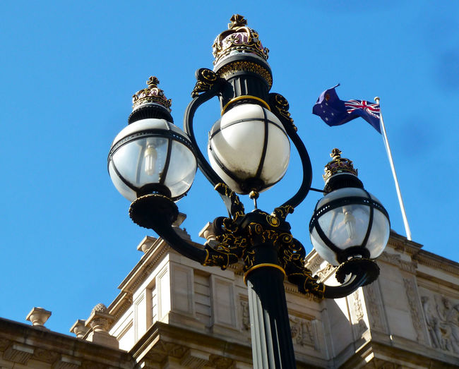 Low angle view of lamp post and australian flag against blue sky