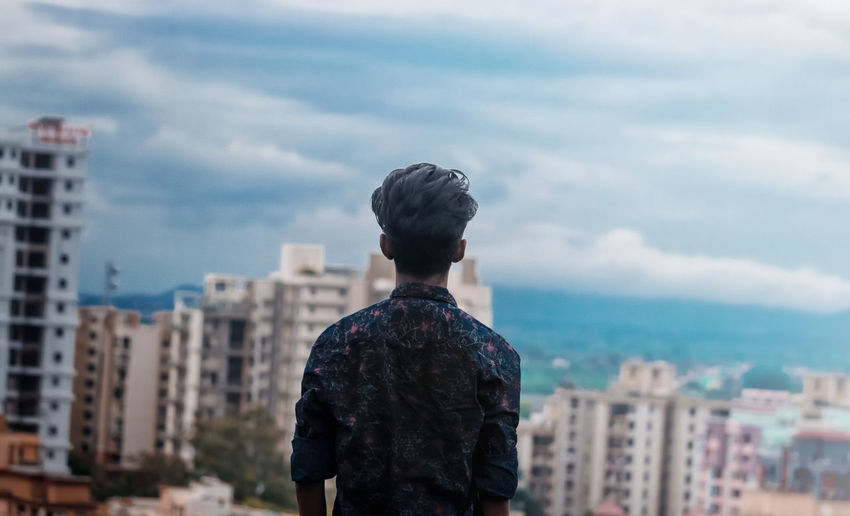 Rear view of man looking at city buildings against sky