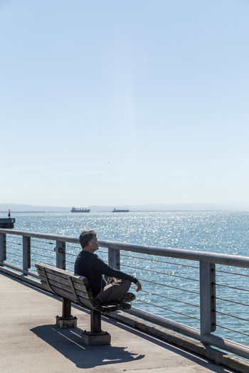 Man sitting on bench looking at sea against clear sky