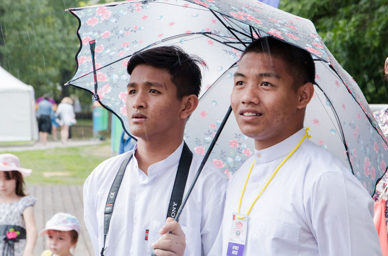 Indonesian guys in the rain Adult Clothing Day Focus On Foreground Headshot Incidental People Males  Mature Men Men Mid Adult Mid Adult Men Outdoors Portrait Protection Rain Real People Security Standing Togetherness Two People Young Adult Young Men