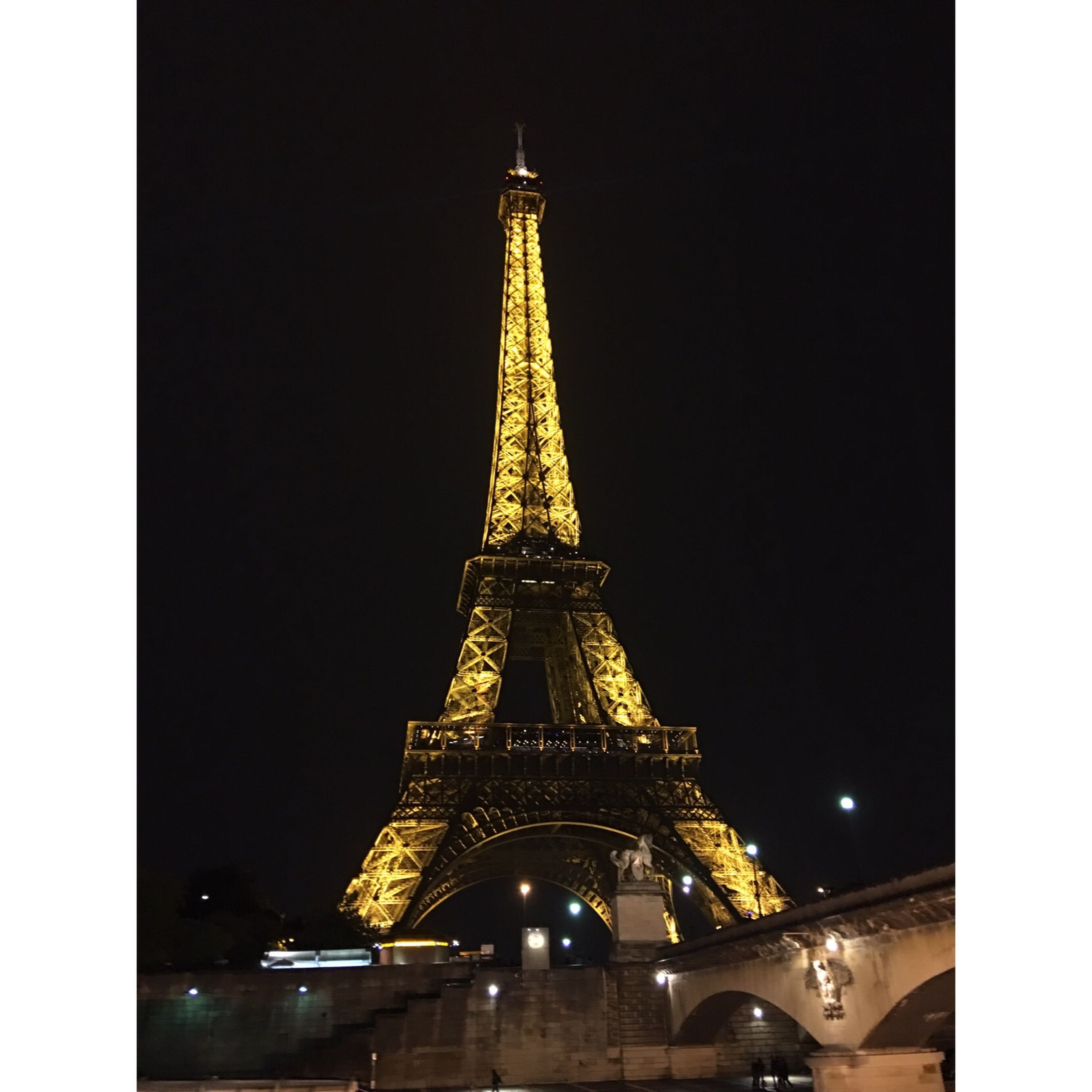 eiffel tower, tower, international landmark, travel destinations, night, famous place, built structure, architecture, tourism, illuminated, capital cities, tall - high, metal, culture, low angle view, building exterior, spire, sky, city, architectural feature, tall, outdoors, history, skyscraper, monument, no people