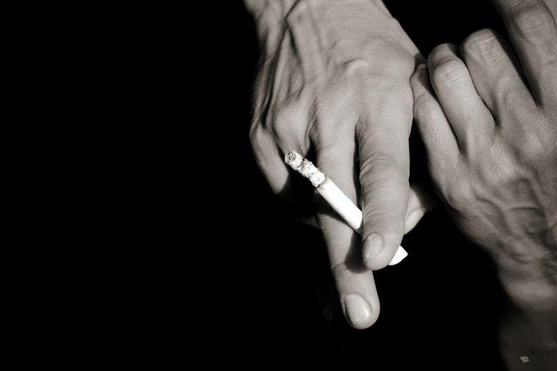 Close-up of man holding cigarette against black background