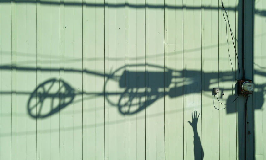 Shadow Focus On Shadow Sunlight Pattern Wall - Building Feature Metal Utility Utility Pole Electricity  Electric Lines Power Line  Arms Raised Arm Reaching Hand Overhead Siding Corrugated Electrocution Hazard Danger Safety Power Pole Cable Internet Service Metal Building Meter Grid Energy Hazardous Harmful Fatal