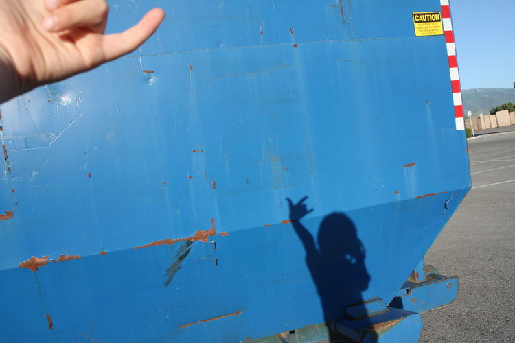Shadow of child showing rock sign on blue metallic structure during sunny day