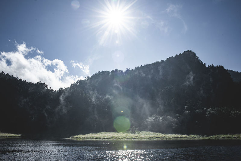 Sunlight streaming through lake against sky on sunny day
